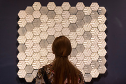 "© Licensed to London News Pictures. 11/09/2018. LONDON, UK. A staff member views upcycled tiles made by ""Trashpresso"", designed by Miniwiz, a mobile solar-powered recycling plant, at a preview of the 87 nominees for the eleventh Beazley Designs of the Year exhibition and awards at the Design Museum in Kensington.  The exhibition runs 12 September to 6 January 2019 and celebrates the most innovative designs of the last year.  Photo credit: Stephen Chung/LNP"