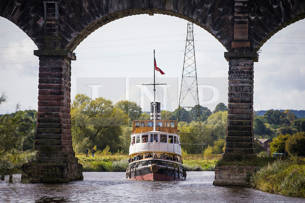 """© Licensed to London News Pictures. 30/09/2016. Bartington UK. Picture shows the Daniel Adamson making it's way under the Dutton rail viaduct on the River Weaver on it's maiden voyage after a £5M renovation. The Daniel Adamson steam boat has been bought back to operational service after a £5M restoration. The coal fired steam tug is the last surviving steam powered tug built on the Mersey and is believed to be the oldest operational Mersey built ship in the world. The """"Danny"""" (originally named the Ralph Brocklebank) was built at Camel Laird ship yard in Birkenhead & launched in 1903. She worked the canal's & carried passengers across the Mersey & during WW1 had a stint working for the Royal Navy in Liverpool. The """"Danny"""" was refitted in the 30's in an art deco style. Withdrawn from service in 1984 by 2014 she was due for scrapping until Mersey tug skipper Dan Cross bought her for £1 and the campaign to save her was underway. Photo credit: Andrew McCaren/LNP"""