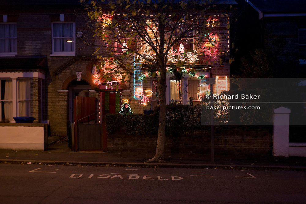 A residential house is adorned with a mass of wasteful Christmas lights, the only one in this south London street.