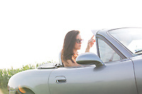 Woman reading map in convertible against clear sky on sunny day