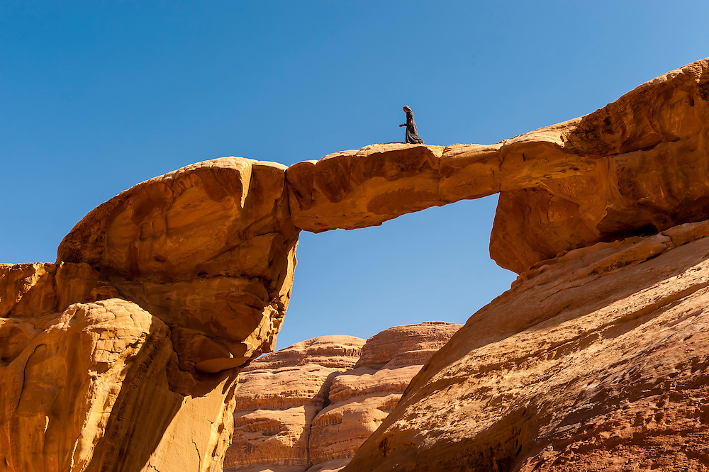 A Bedouin boy atop the 100 foot tall (35 meters) Burdah Rock Bridge (an arch), Wadi Rum, in the Arabian Desert, Jordan.