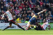 Arsenal forward Olivier Giroud (12) is tackled by Sunderland's Midfielder Lamine Kone (23) and Sunderland's Midfielder Yann M'Vila (21) during the Barclays Premier League match between Sunderland and Arsenal at the Stadium Of Light, Sunderland, England on 24 April 2016. Photo by George Ledger.