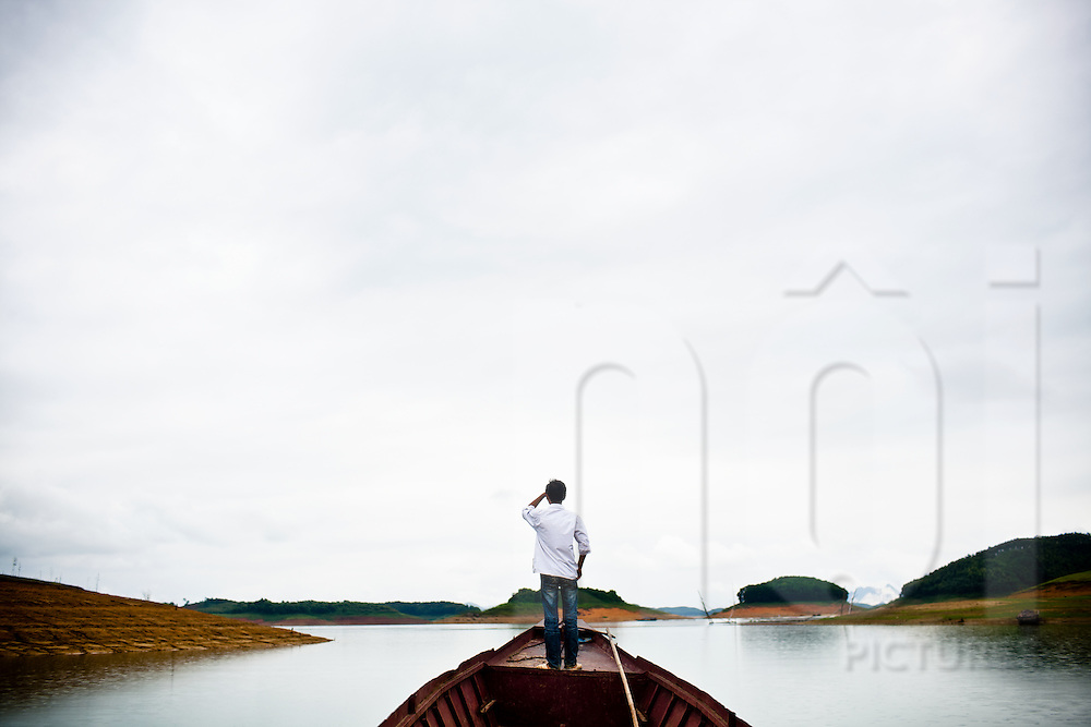 A young boy navigates a boat through the many islands of Thac Ba Reservoir in northern Vietnam, Asia.