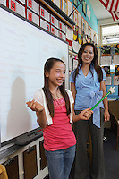 Schoolgirl and teacher standing in front of projection screen and smiling