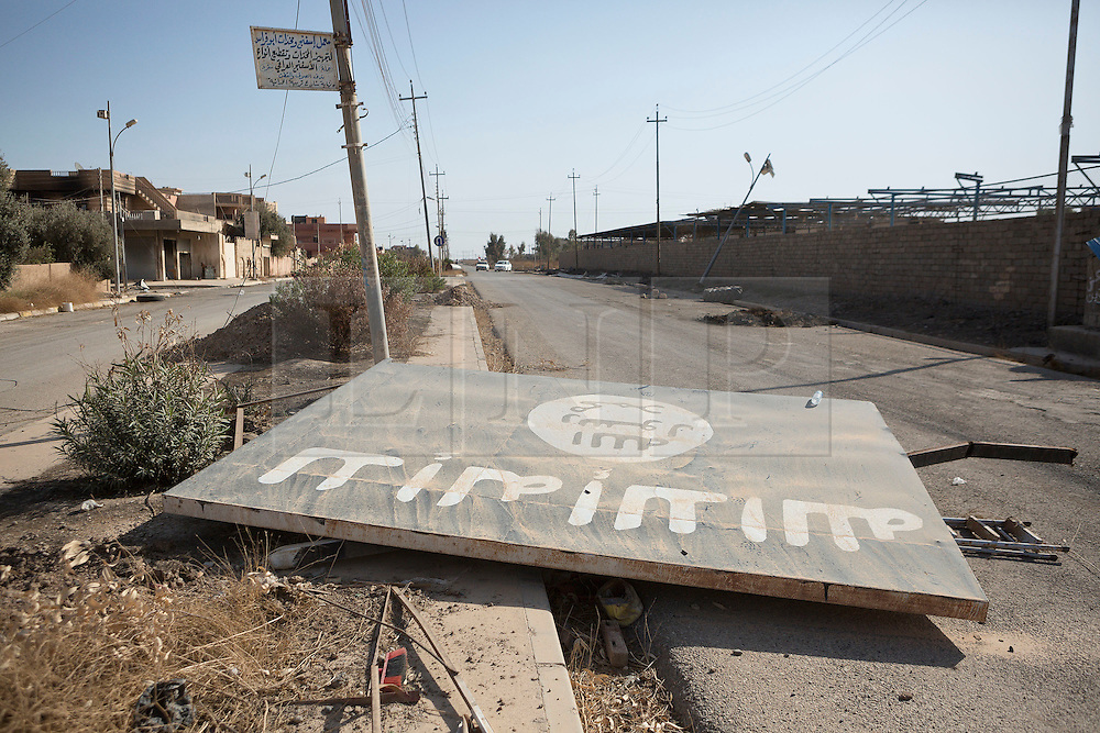 © Licensed to London News Pictures. 04/11/2016. Hamdaniyah, Iraq. A board bearing the flag of the Islamic State lies on the ground in the recently liberated Christian town of Hamdaniyah, Iraq.<br /> <br /> Although located close to a front line, littered with improvised explosive devices and pieces of unexploded ordnance the Christian town of Hamdaniyah has only recently been cleared of ISIS extremists who stayed behind to fight. After the town's liberation as part of the Mosul Offensive residents and priests of the town are now free to take short trips to assess damage, salvage possessions and clear up the mess left by militants during their two year occupation.<br /> <br /> Hamdaniyahh, and much of the Nineveh plains, were captured by the Islamic State during a large offensive on the 7th of August 2014 that saw the extremists advance to within 20km of the Iraqi Kurdish capital Erbil. Residents of the town, who included many Christian refugees who escaped there after the fall of Mosul, were then forced to seek sanctuary in the Kurdish areas. In the year and two months of the ISIS occupation churches were burnt, homes were put into use as militant accommodation and bomb factories and some buildings destroyed by coalition airstrikes. Photo credit: Matt Cetti-Roberts/LNP