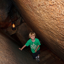 A young boy explores a cave at Lost River Gorge in New Hampshire's White Mountains. North Woodstock.