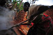 12-03-31   -- KAMPALA, UGANDA  -- Alcohol is often seen as the only way out of the depression faced by most residents of the Acholi Quarter. Margret Abilo, seen roasting millet in preparation for making a local brew, says she does brisk business.  Photo by Daniel Hayduk