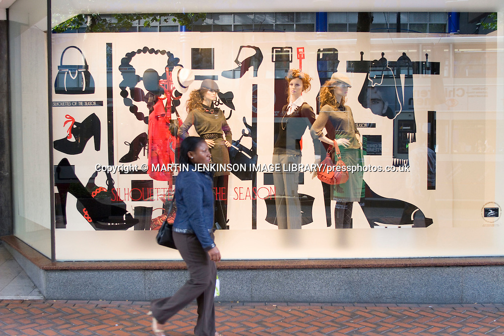 Shopper walking past a display of womens clothing in a department store window Corporation Street Birmingham ......
