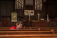 Jacob Dickson of Tucson joined with fellow Up With People cast members to wash down the pews at the Congregational Church Wednesday morning.  (Karen Bobotas/for the Laconia Daily Sun)