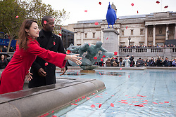 © Licensed to London News Pictures. 11/11/2013. London, UK. Actress Zoe Tapper (L) and actor Adrian Lester throw poppies into one of Trafalgar Square's fountains after the 'Silence in the Square' ceremony, held by the Royal British Legion in London today (11/11/2013). The ceremony, culminating in a two minutes silence and the placing of poppies into the square's fountains, is held on the 11th hour of the 11th day to commemorate the signing of the armistice that ended the First World War.  Photo credit: Matt Cetti-Roberts/LNP