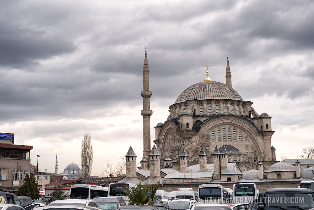 Nuruosmaniye Mosque towers over the Çemberlitaş neighborhood in the Gatih district of Istanbul, with the New Mosque (Yeni Camii) in the background at left. Nuruosmaniye Mosque, standing next to Istanbul's Grand Bazaar, was completed in 1755 and was the first and largest mosque to be built in Ottoman Baroque style.
