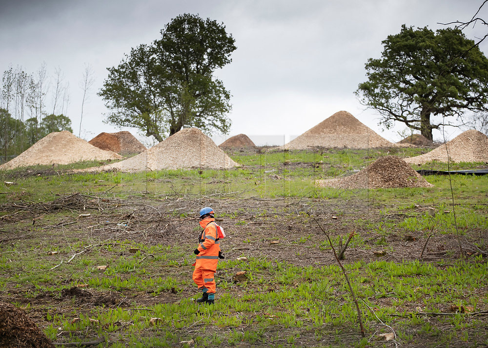 © Licensed to London News Pictures. 28/04/2019. London, UK. A security guard walks near mounds of shredded trees at the High Speed 2 works in the Colne Valley west of London. Extinction Rebellion activists have joined with Stop HS2 protestors to occupy trees in Colne Valley to stop their felling for the HS2 rail project. Workers were expected to start cutting down the trees yesterday and to continue today but the protests have stopped the work. Photo credit: Peter Macdiarmid/LNP
