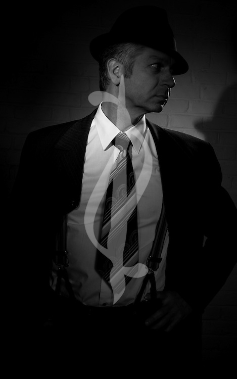 Male model posing in detective outfit.