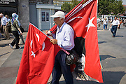08 AUGUST 2007 -- ISTANBUL, TURKEY: A man sells Turkish flags in Istanbul, Turkey. Istanbul, a city of about 14 million people, and the largest city in Turkey, straddles the Bosphorus Straits between Europe and Asia. It is one of the oldest cities in the world. It was once the center of the Eastern Roman Empire and was called Constantinople, named after the Roman Emperor Constantine. In 1453, Mehmet the Conqueror, Sultan of the Ottoman Empire, captured the city and made it the center of the Ottoman Turkish Empire until World War I. After the war, the Ottoman Empire was dissolved and modern Turkey created. The capitol was moved to Ankara but Istanbul (formerly Constantinople) has remained the largest, most diverse city in Turkey.    Photo by Jack Kurtz