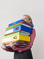 Female office worker carrying heavy binders on white background