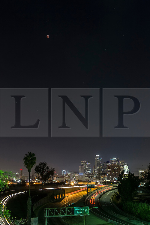 © Licensed to London News Pictures. 08/10/2014. Los Angeles, UK A Blood moon total lunar eclipse visible in the night sky over downtown Los Angeles, and much of the west coast of North America in the early hours of Wednesday. Photo credit : David Fearn/LNP. Photo credit : David Fearn/LNP