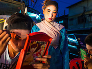 16 JANUARY 2015 - BANGKOK, THAILAND: Performers with the Sai Yong Hong Opera Troupe get into character before performing at the Chaomae Thapthim Shrine, a Chinese shrine in a working class neighborhood of Bangkok near the Chulalongkorn University campus. The troupe's nine night performance at the shrine is an annual tradition and is the start of the Lunar New Year celebrations in the neighborhood. Lunar New Year, also called Chinese New Year, is officially February 19 this year. Teochew opera is a form of Chinese opera that is popular in Thailand and Malaysia.    PHOTO BY JACK KURTZ