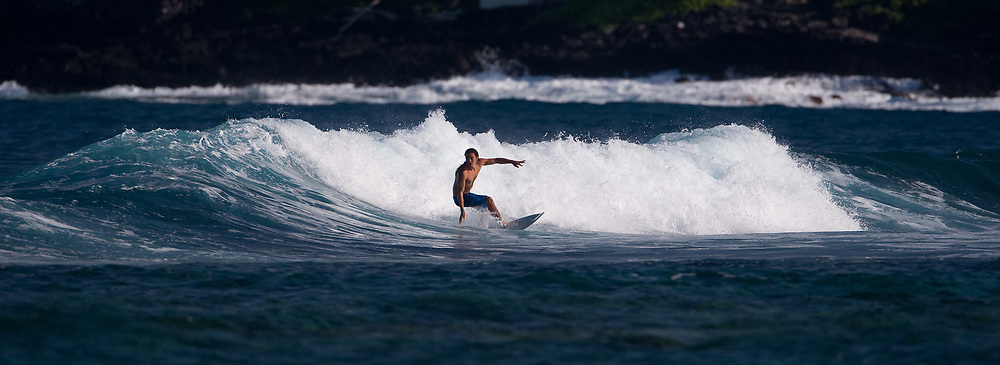 An unidentified surfer tackles the early morning waves offshore in Kahaluu Bay at Kahaluu Beach Park in Keauhou on the Big Island of Hawaii.