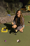 Freeport, New York, U.S. September 6, 2013. BRITTNEY SCANNELL, 17, from Baldwin, plays a night game of miniature golf at Crow's Nest Mini Golf at the Nautical Mile.