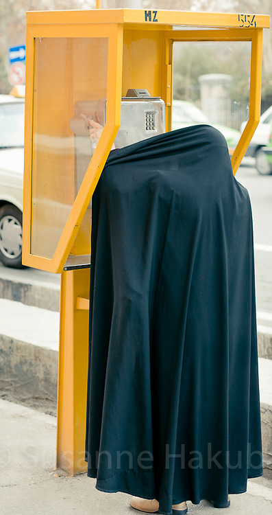 Woman in chador using phone box , Tehran, Iran.