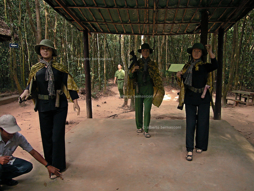 "Vietnam, Cu Chi, viet women guerrilla. visitors are greeted by a sign reading: ""Please try to be a Cu Chi guerrilla. Wear these uniforms before entering tunnel."" Black pajamas, pith helmets, rubber sandals and old rifles are available."