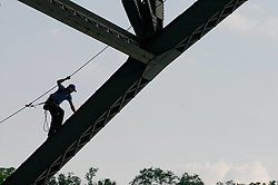 A rigger supporting aerial-acrobats makes his way up on the ovespan construction underneath the Strawberry Mansion Bridge. (Bastiaan Slabbers/for PhillyVoice)