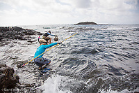 A pair of spearfishermen enter the water. Big Island of Hawaii.