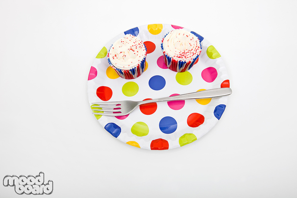High angle view of cupcakes in multicolored plate against white background