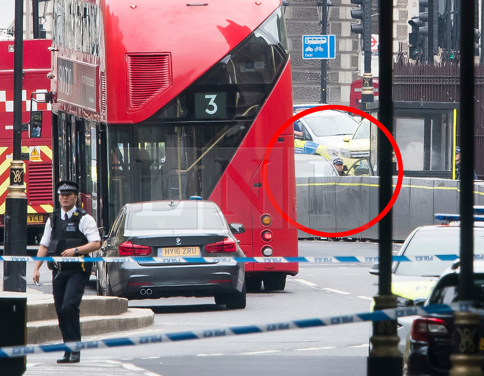 © Licensed to London News Pictures. 14/08/2018. London, UK. A police officer is seen examining a car (circled red) which rammed the security barriers at the Houses of Parliament in London. It has been reported that pedestrians were hit by the car. Photo credit: Ben Cawthra/LNP