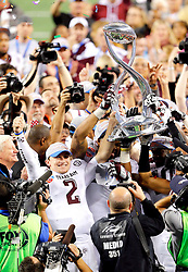 Texas A&M quarterback, Johnny Manziel (2) and teammates hoist the AT&T Cotton Bowl Classic trophy after the Aggies defeated the Oklahoma Sooners 41-13 at Cowboys Stadium in Arlington.