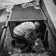 """Roma - Giardini di fronte alle Terme di Diocleziano. Abdul 16 anni, egiziano, mentre scende nel """"buco"""", un cunicolo sotto la strada, che viene coperto da una grata arrugginita, dove dove dormono i ragazzini, per lo piu minorenni, l'aria è irrespirabile dalla puzza di escrementi, dentro c'è di tutto, valige indumenti usati , animali morti e rifiuti di ogni genere. A 400 metri c'è la Stazione Termini e dall'altra parte della strada passano turisti ignari che vanno in visita alle Terme di Diocleziano."""