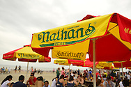 Brooklyn, New York, USA. 10th August 2013. Outside Nathan's Famous boardwalk restaurant, the picnic tables, with colorful red yellow and green umbrellas, are filled with people eating during the 3rd Annual Coney Island History Day celebration.