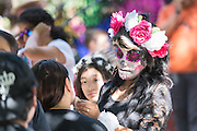 A young woman applies costume make up to to look like a skeleton for the Day of the Dead festival in the Jardin Principal in San Miguel de Allende, Guanajuato, Mexico. The week-long celebration is a time when Mexicans welcome the dead back to earth for a visit and celebrate life.