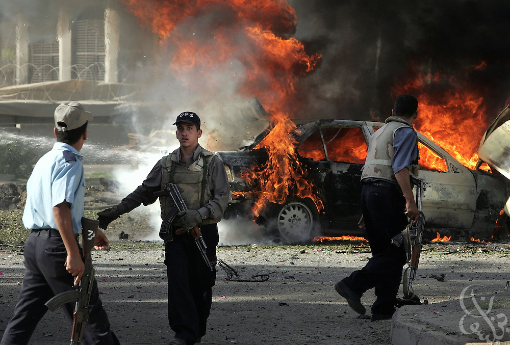 Iraqi policemen secure the scene of a morning May 25, 2004 car bomb attack outside the Karma hotel in Baghdad, Iraq.