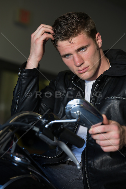 All American man sitting on a Motorcycle in an auto repair shop fixing his hair