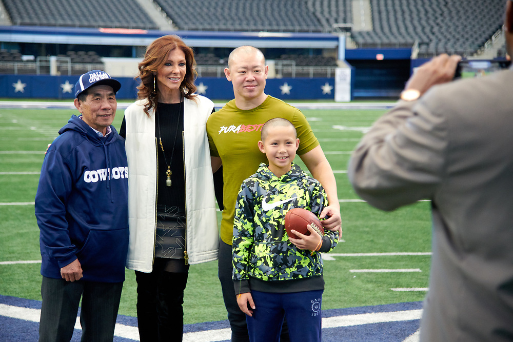 Charlotte Jones Anderson poses for a photo with visitors on the football field at AT&T Stadium in Arlington, Texas on December 12, 2017. (Cooper Neill for The New York Times)