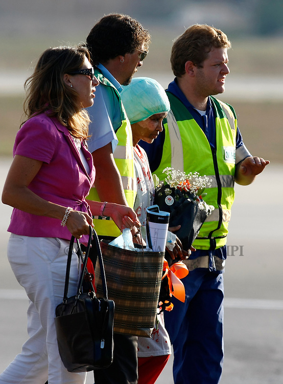 Shwejga Mullah (3rd L) of Ethiopia is helped to a waiting ambulance after arriving at Malta International Airport,outside Valletta September 15, 2011. An Ethiopian nanny in the Gaddafi household who suffered horrific burns after she did not stop one of Muammar Gaddafi's grandchildren crying, has arrived in Malta for specialised medical treatment. Shwejga Mullah was recently discovered weak and alone in the home abandoned by Muammar Gaddafi's son Hannibal. She said that  Hannibal Gaddafi's wife Aline threw boiling water over her when she did not stop Hannibal Gaddafi's daughter crying and refused to beat the child. The nanny was brought over in a private plane chartered by the Maltese government.    REUTERS/Darrin Zammit Lupi (MALTA)
