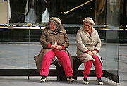 Identical and eccentric twin sisters wait for buses at a stop's shelter in central Brussels.