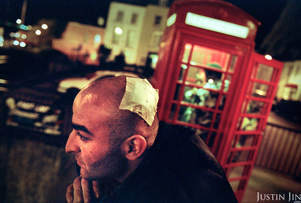 An Iraqi asylum seekers stands near a phone box in Dover. He came from the notorious Red Cross refugee camp in Sangatte. He smuggled himself under a lorry from Calais. The truck driver hit him with an iron bar when he found the refugee hidden in his truck upon reaching England. Drivers are fined heavily if they were caught with an asylum seeker in their vehicle...Picture taken April 2002 by Justin Jin. Copyright 2002 by Justin Jin.