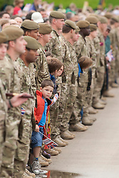 © Licensed to London News Pictures. 30/06/2012. National Memorial Arboretum, Staffordshire, UK. The Olympic Torch Relay visited the National Memorial Arboretum in Staffordshire earlier today. Cpl Johnson Beharry VC carried the Olympic Torch along the causeway, climbed the steps and paused at the Armed Forces Memorial to remember the fallen.Pictured, a youngster peers around the line of soldiers to get a better view of the Olympic flame. Photo credit : Dave Warren/LNP