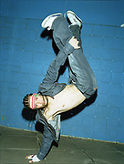 Young man doing a one arm handstand with legs in air.
