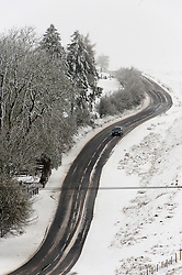 © Licensed to London News Pictures. 04/04/2019. Builth Wells, Powys, Wales, UK. Motorists drive along the B4520 road through a wintry landscape on the Mynydd Epynt range between Builth Wells and Brecon in Powys, UK. Photo credit: Graham M. Lawrence/LNP
