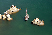 A small tourist boat navigates between rocks off the coast line near Praia Da Rocha, Portimão in the Algarve, Portugal.