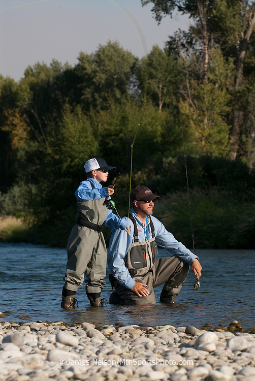 A nine-year old boy casts a fly with his father on the South Fork of the Snake River, Idaho.