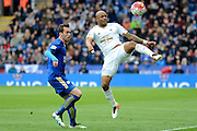 Swansea City striker Andre Ayew controls the ball watched by Leicester City defender Christian Fuchs  during the Barclays Premier League match between Leicester City and Swansea City at the King Power Stadium, Leicester, England on 24 April 2016. Photo by Alan Franklin.