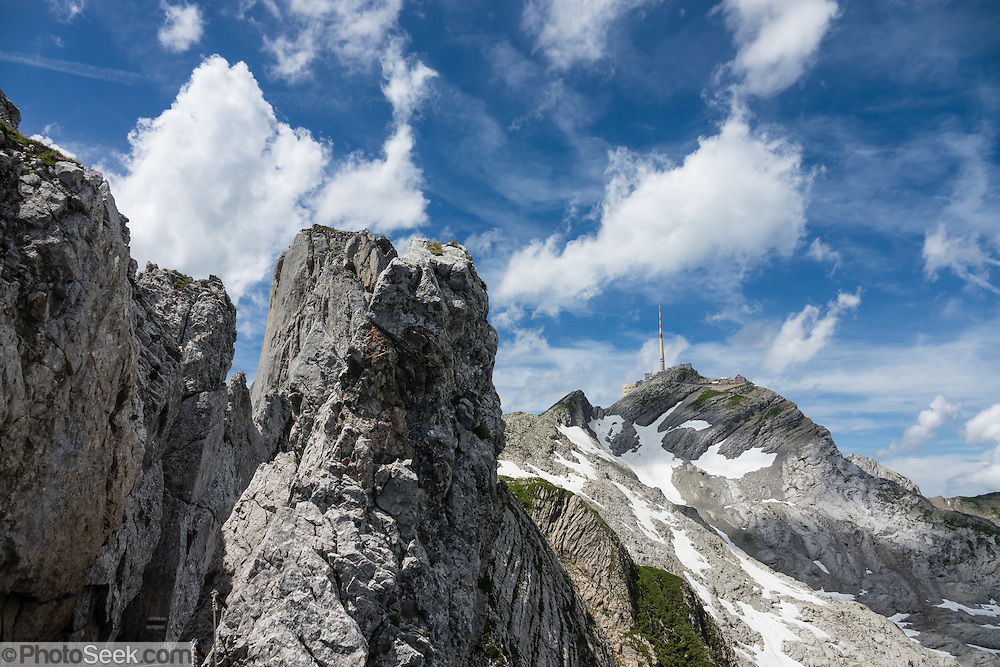 Weaving through limestone outcroppings, we hiked the stunning Lisengrat, a sinuous chain-protected trail from Rotsteinpass to the summit of Säntis. The Lisengrat is a magnificent ridge route between Säntis (2502 m / 8218 feet elevation) and Altmann (2435 m / 7989 ft), the two highest peaks in Appenzell's Alpstein range. The rocky route is safe, but can be scary for those with fear of heights. Shared by three cantons, Säntis can be reached easily via cable car or with effort via trails, to see vast mountain views across six countries: Switzerland, Germany, Austria, Liechtenstein, France and Italy. The Appenzell Alps rise between Lake Walen and Lake Constance.