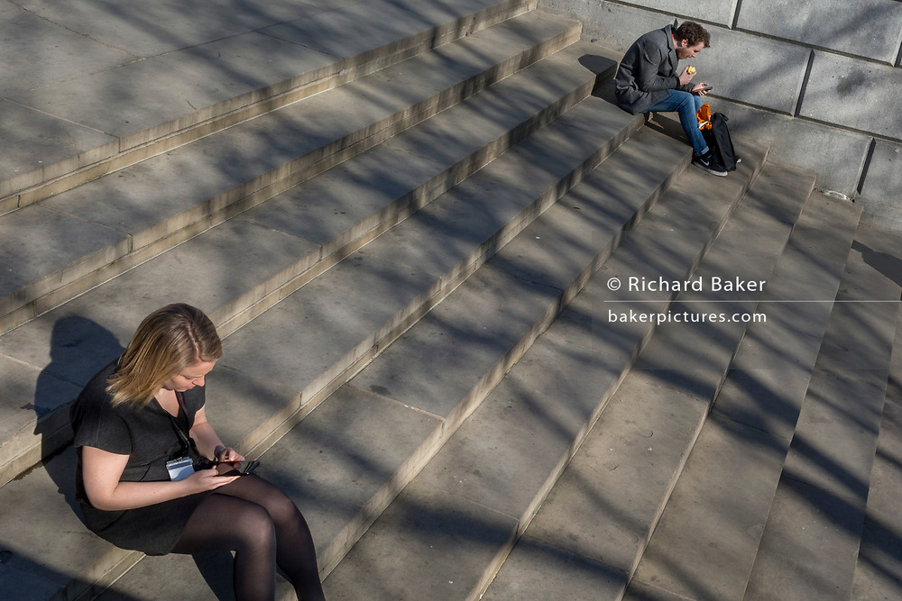 Two people sit and use their mobile phones on the steps beneath the Fourth Plinth in Trafalgar Square, on 26th February, in London, England.