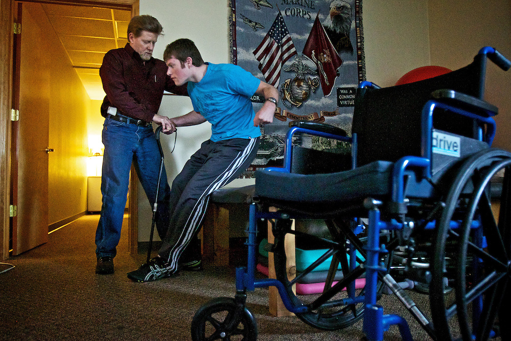 David Carson is assisted by Kevin Sgroi, owner of Joshua Tree Physical Therapy, during a therapy session Friday. Carson was hospitalized nearly six months after a friend restrained him with a chokehold during a 2010 New Year's Eve party in Post Falls.