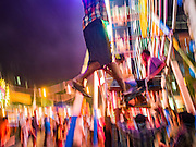 29 OCTOBER 2015 - YANGON, MYANMAR: Workers on a human powered Ferris Wheel during a street carnival in central Yangon. Electricity is scarce in Myanmar, especially in rural areas, and most traveling carnivals use human powered rides. Workers climb to the top of the Ferris Wheel and then pull it around getting it spinning. They do the same with Merry Go Rounds, but instead of climbing to the top they pull it around. The carnival coincided with the Thadingyut Festival, the Lighting Festival of Myanmar, which is held on the full moon day of the Burmese Lunar month of Thadingyut, October or November on the Gregorian calendar. The carnival featured food, rides and games.      PHOTO BY JACK KURTZ