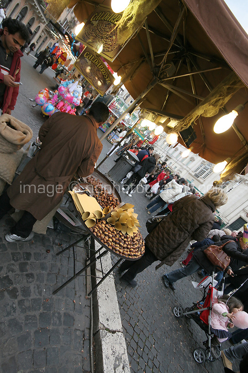 Street vendor selling roast chestnuts at an outdoor square market in Rome Italy
